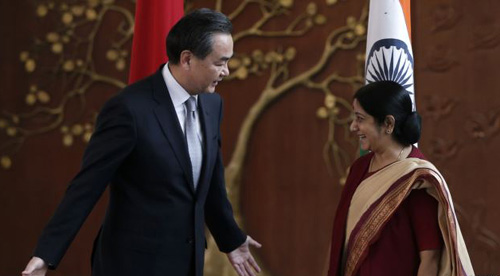 Chinese Foreign Minister Wang Yi (left) gestures to his Indian counterpart Sushma Swaraj before their meeting in New Delhi on June 8, 2014. /Reuters