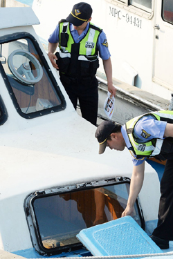 Police officers search a ship in Mokpo, South Jeolla Province on Sunday.