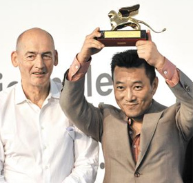Curator Cho Min-suk holds up the Golden Lion award for the Best National Participation at the award ceremony of the 14th International Architecture Exhibition of the Venice Biennale, in Venice, Italy on Saturday. At left is Biennale director Rem Koolhaas. /AP-Newsis