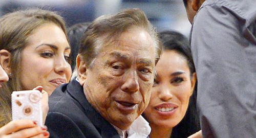Los Angeles Clippers owner Donald Sterling (center) and V. Stiviano (right) watch the Clippers play the Sacramento Kings. /AP