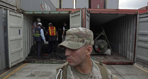 A police officer stands guard as investigation officers look inside a container holding military equipment aboard the North Korean-flagged freighter Chongchongang at the international container terminal at Colon City, Panama. /AP