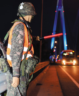 A soldier stops cars in a nationwide manhunt for ferry owner Yoo Byeong-eon in Jindo, South Jeolla Province on Thursday. /Newsis
