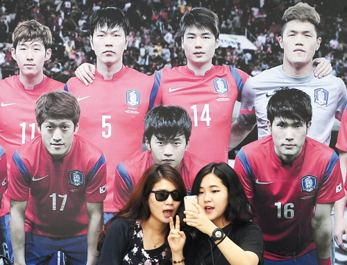 Women take a souvenir photo with a picture of Korean national soccer team players in Seoul on Monday. /AP-Newsis