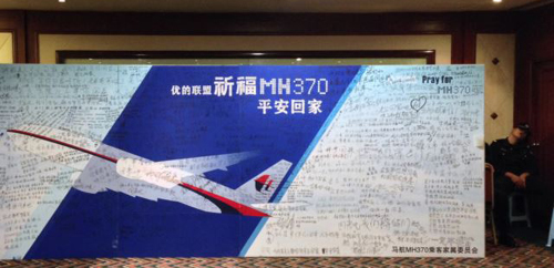 A policeman takes a nap beside a board written with messages for passengers onboard the missing Malaysia Airlines Flight MH370 during a closed meeting held between Malaysian representatives and Chinese relatives of passengers on Flight MH370 at Lido Hotel. /Reuters