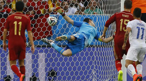 Spains goalkeeper Iker Casillas dives trying to save a ball from Chiles Charles Aranguiz (not pictured) during their 2014 World Cup Group B soccer match at the Maracana stadium in Rio de Janeiro on June 18, 2014. /Reuters