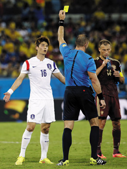 Ki Sung-yueng reacts as he is shown the yellow card by referee Nestor Pitana during the match between Korea and Russia at the Arena Pantanal in Cuiabá, Brazil on Tuesday. /AP-Newsis