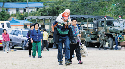 Villagers hurry to a shelter in Goseong, Gangwon Province on Sunday as a conscript is at large after a deadly shooting spree.