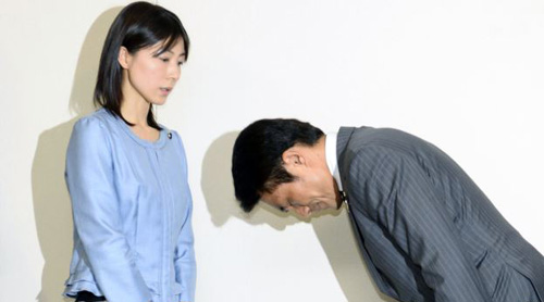 Tokyo city assembly lawmaker Akihiro Suzuki (right) bows to apologize to female lawmaker Ayaka Shiomura at Tokyo Metropolitan City Hall, in this photo taken by Kyodo on June 23, 2014. /Reuters