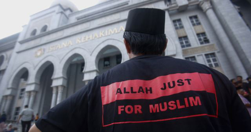 A Muslim man stands outside the court in Putrajaya outside Kuala Lumpur on June 23, 2014. /Reuters