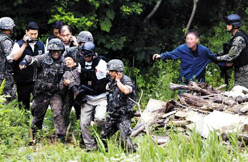 Soldiers take a conscript who went on a shooting spree, from his hideout after a botched suicide attempt, in Goseong, Gangwon Province on Monday.