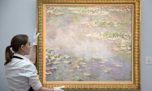 A gallery assistant poses with the painting Nympheas by Claude Monet at a photo-call for Impressionist and Modern Art Evening Sale at Sothebys auction house in London on June 18, 2014. /Reuters