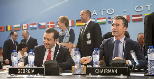 NATO Secretary-General Anders Fogh (right) and Georgian Defense Minister Irakli Alasania take their seat at a meeting of the NATO-Georgia Commission at NATO headquarters in Brussels, Belgium. /AP