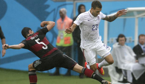 Germanys Mats Hummels (left) and United States Fabian Johnson challenge for the ball during the group G World Cup soccer match between the U.S. and Germany at the Arena Pernambuco in Recife, Brazil on June 26, 2014. /AP