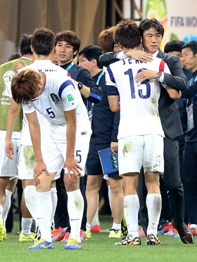 Korean national football team manager Hong Myung-bo hugs a player after a loss against Belgium in the 2014 FIFA World Cup at the Arena de São Paulo Stadium in Brazil on Thursday. /News 1