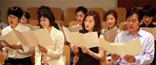Artists practice for a music video marking Pope Francis' visit, at Myeongdong Cathedral in Seoul on Monday. Counterclockwise from front left, model Hong Jin-kyung, news presenter Hwang Jung-min, actors Kim Ha-neul and Ahn Sung-ki, singer Yoon Gun, and actors Lee Yun-ji and Kim Kang-woo