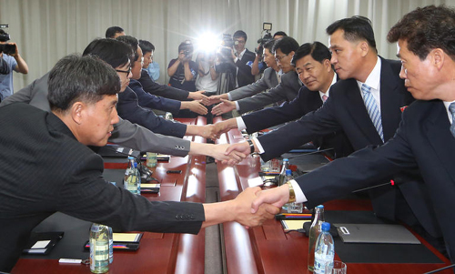 Officials from the two Koreas shake hands before a meeting at the joint Kaesong Industrial Complex on Thursday. /News 1