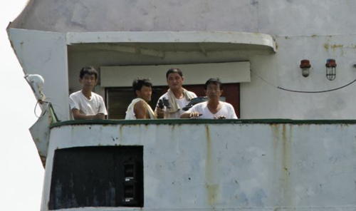 North Korean sailors look out from the deck of their cargo ship Chong Chon Gang in Sherman Bay near Colon City, Panama on Feb. 12, 2014. /AP