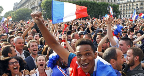 French soccer fans celebrate after France scored the first goal, as they watch the World Cup soccer match between France and Nigeria being shown live on a giant screen, in front of Paris City Hall on June 30, 2014. /AP