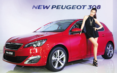 A model poses with Peugeots new 308 hatchback at an exhibition hall in Seoul on Monday.