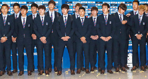 Members of the national football team arrive from Brazil at Incheon International Airport on Monday. On the floor are toffees with which a few disappointed fans pelted them.