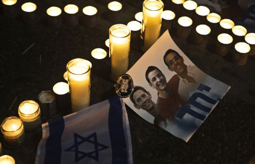 Candles placed next to a picture of three Israeli teenagers who were abducted and killed, in Tel Avivs Rabin Square on June 30, 2014. /Reuters