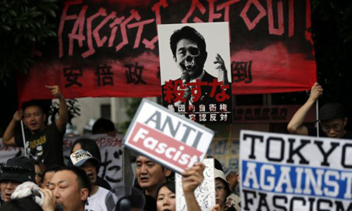 Protesters holding placards shout slogans at a rally against Japans Prime Minister Shinzo Abes push to expand Japans military role in front of Abes official residence in Tokyo on June 30, 2014. /Reuters