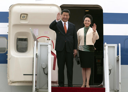 Chinese President Xi Jinping and Chinese first lady Peng Liyuan wave upon their arrival at a military airport in Seongnam in Gyeonggi Province on Thursday. /AP-Newsis