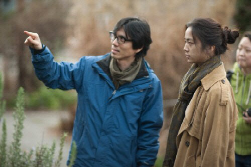 Director Kim Tae-yong talks with Chinese actress Tang Wei on set while shooting the film