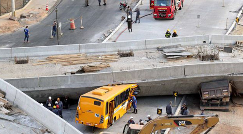 Rescue workers try to reach vehicles trapped underneath an overpass bridge that collapsed while under construction in Belo Horizonte, Brazil on July 3, 2014. /Reuters