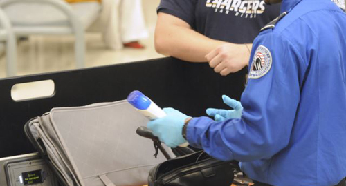 A Transportation Security Administration (TSA) official checks a passengers carry-on luggage at a security checkpoint at Hartsfield-Jackson Atlanta International Airport in Atlanta. /AP