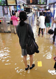 Passengers walk into the flooded Hongdaeipgu Station on Subway Line No. 2 in Seoul on Wednesday night. /News 1
