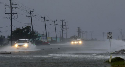 Vehicles navigate a flooded Highway 64 as wind pushes water over the road as Hurricane Arthur passes through Nags Head, North Carolina on July 4, 2014. /AP