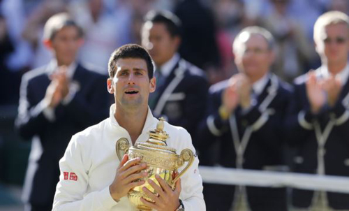 Novak Djokovic of Serbia reacts while holding the winners trophy after defeating Roger Federer of Switzerland in their mens singles finals tennis match on Centre Court at the Wimbledon Tennis Championships in London on July 6, 2014. /Reuters