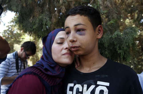 Tariq Khdeir (right) is greeted by his mother after being released from jail in Jerusalem on July 6, 2014. /Reuters