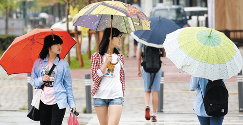 Pedestrians walk in rain in Gwangju on Sunday as the monsoon hit the southern part of the country.