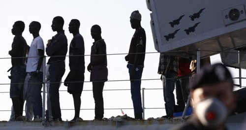 Migrants disembark from a navy ship in the Sicilian harbour of Pozzallo on June 30, 2014. /Reuters
