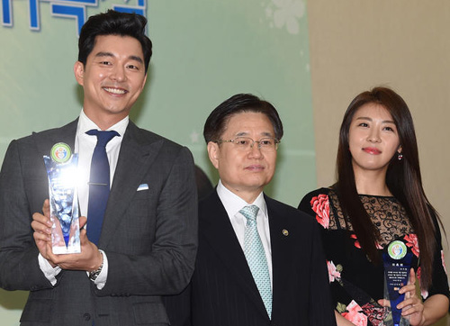 Gong Yoo (left) and Ha Ji-won (right) pose with National Tax Service Commissioner Kim Duk-jung after being appointed promotional ambassadors for the authority on Monday. /News 1
