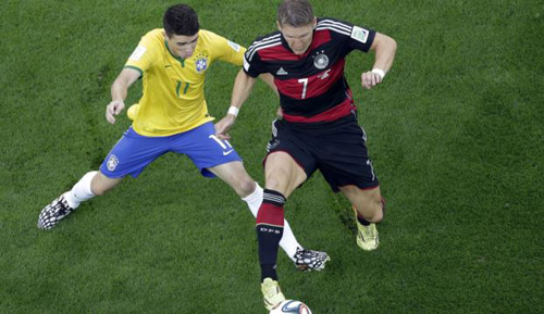 Brazils Oscar (left) and Germanys Bastian Schweinsteiger vie for the ball during the World Cup semifinal soccer match between Brazil and Germany at Mineirao Stadium in Belo Horizonte, Brazil on July 8, 2014. /AP