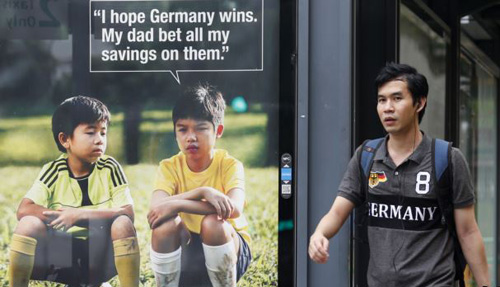 A man walks past a World Cup anti-gambling advertisement at a taxi stand in Singapore on July 9, 2014. /Reuters