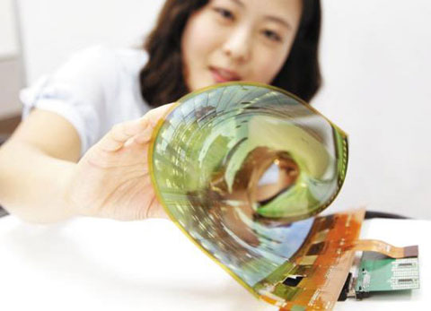 An LG Display staffer rolls up the firms 18-inch bendable display at a workshop in Gyeonggi Province on Thursday. /Courtesy of LG Display