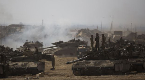 Israeli soldiers stand atop a tank at a staging area near the border with the Gaza Strip on July 13, 2014. /Reuters