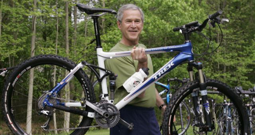 President George W. Bush lifts his bicycle before taking a mountain bike ride in Beltsville, Maryland. /AP