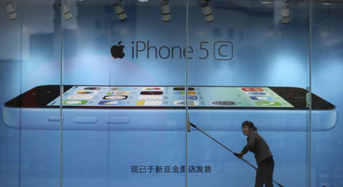 Worker cleans glass in front of an iPhone 5C advertisement at an apple store in Kunming, Yunnan province, China on Oct. 27, 2013. /Reuters