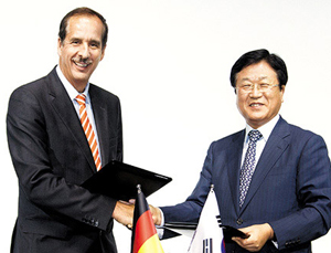 Samsung SDI president Park Sang-jin (right) shakes hands with BMW purchasing chief Klaus Draeger after signing a memorandum of understanding at the BMW driving center in Incheon on Monday. /Courtesy of Samsung SDI
