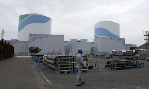 An employee of Kyushu Electric Power walks in front of reactor buildings at the companys Sendai nuclear power plant in Satsumasendai, Kagoshima prefecture. /Reuters