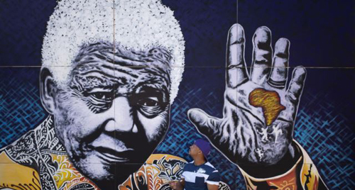 South African artist John Adams works on a giant acrylic-on-canvas painting of Nelson Mandela in the driveway of his house, Johannesburg on July 15, 2013. /AP