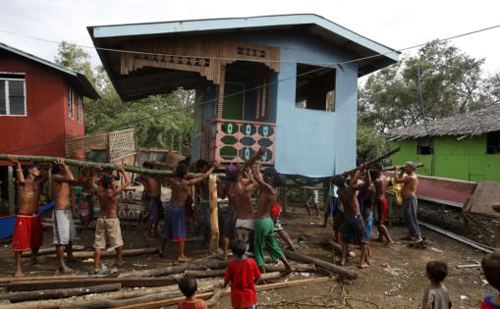 Residents lift a house damaged by Typhoon Rammasun in Batangas city, south of Manila on July 17, 2014. /Reuters