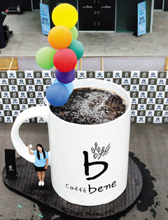 A Caffé Bene staffer poses next to the world's largest mug at the coffee franchise's plant in Yangju, Gyeonggi Province, on Thursday. /News1