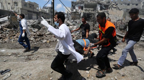 Palestinian medics carry a man injured in Gaza Citys Shijaiyah neighborhood that came under fire as Israel widened its ground offensive against Hamas in the northern Gaza Strip on July 20, 2014. /AP