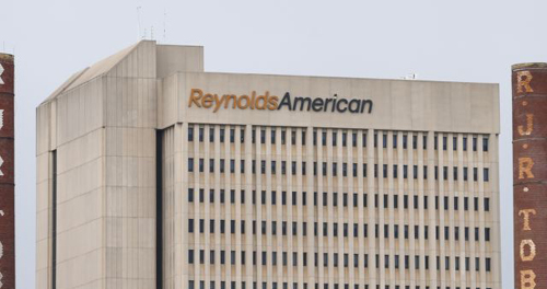 The headquarters of Reynolds American is seen next to the old R.J. Reynolds Tobacco smoke stacks from a previous manufacturing plant in downtown Winston-Salem, North Carolina on May 23, 2014. /Reuters